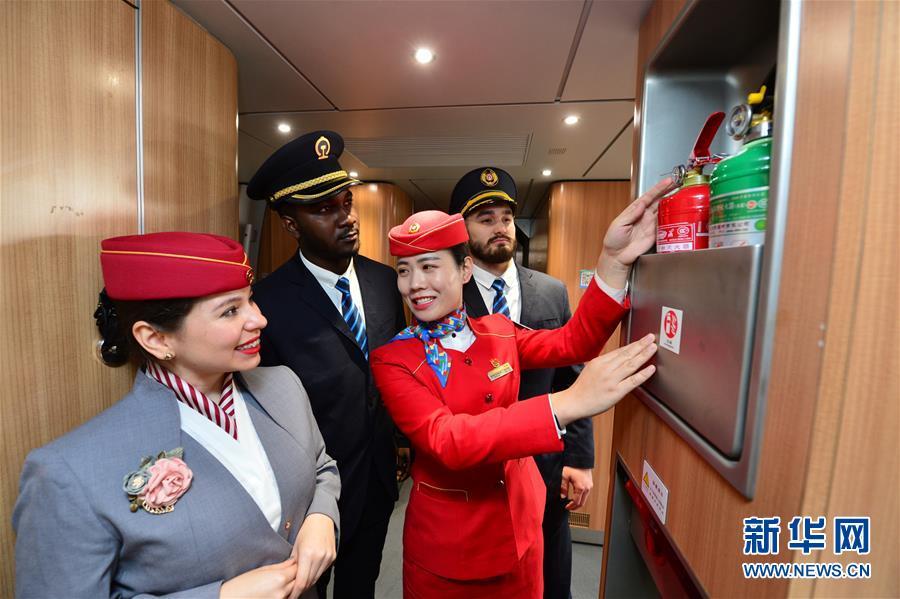 在西安北站动车组列车上,列车长(左三)向留学生志愿者讲解消防器材